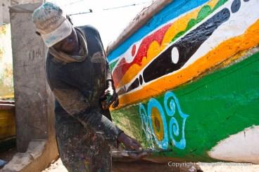 A man doing a paint job on an old fisherman pirogue on N'Dar Tout Atlantic ocean beach in Saint-Louis, Senegal. Photo by Marko Preslenkov.