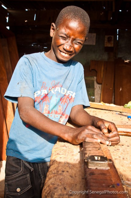 A kid working at carpenter shop in N'Dar Tout quarter of Saint-Louis, Senegal. Photo by Marko Preslenkov.