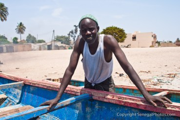 A man taking some time away from repairing the pirogue on the beach in Joal-Fadiout, Senegal. Photo by Marko Preslenkov.