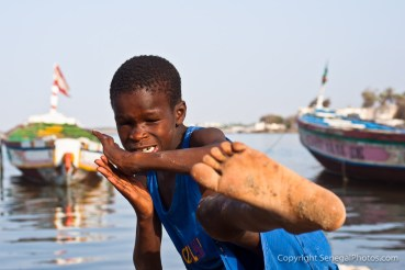 A kids imitating karate kick move on the shores of Senegal river in N'Dar Tout quarter of Saint-Louis, Senegal. Photo by Marko Preslenkov.