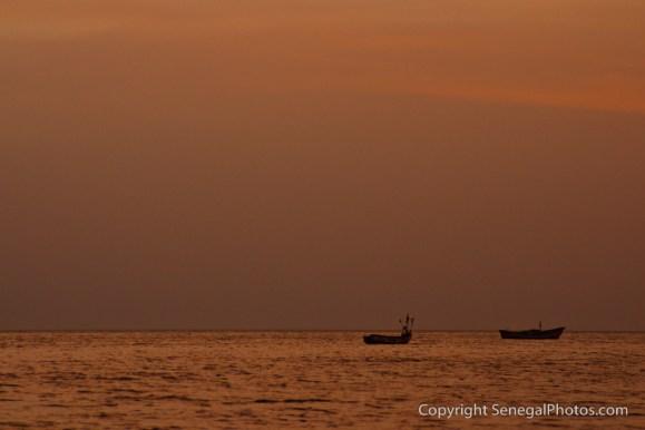 Fishing boats in a last light on the Atlantic ocean in front of village of Joal, Senegal. Photo by Marko Preslenkov.