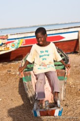 A kid sitting on an old pirogue boat on Senegal river shore in N'Dar Tout quarter of Saint-Louis, Senegal. Photo by Marko Preslenkov.