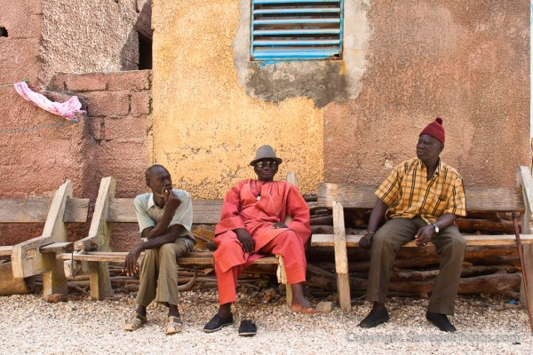 Three friends enjoying the hot afternoon sitting on a wooden bench in Fadiout, Senegal. Photo by Marko Preslenkov.