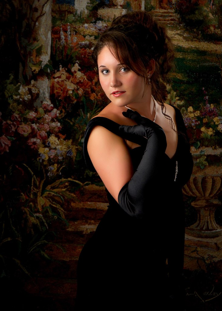 Formal senior pictures of a high school girl standing in front of a tapestry background
