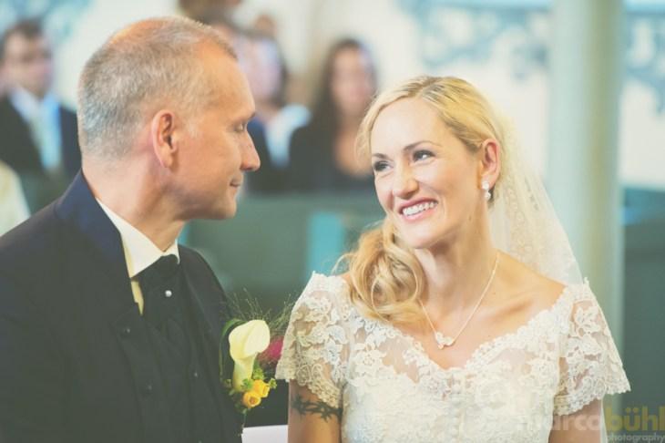 Braut lächelt Bräutigam an Kirche Hochzeit