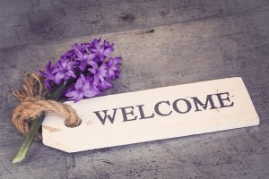 welcome sign with purple flower