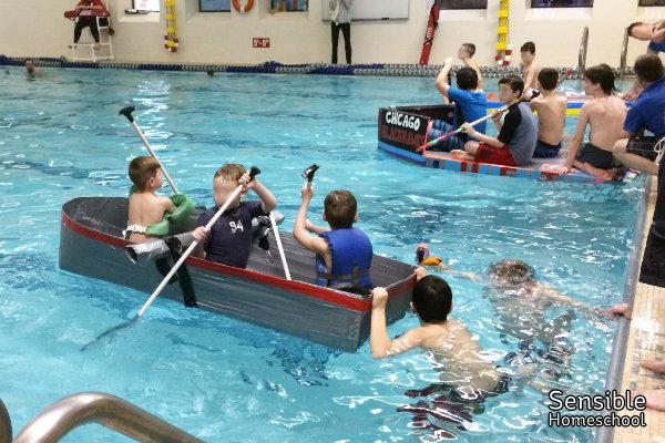 Boys racing DIY cardboard and duct tape boats in indoor YMCA pool