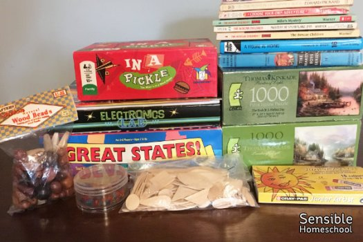 pile of homeschool games, puzzles, books and art supplies