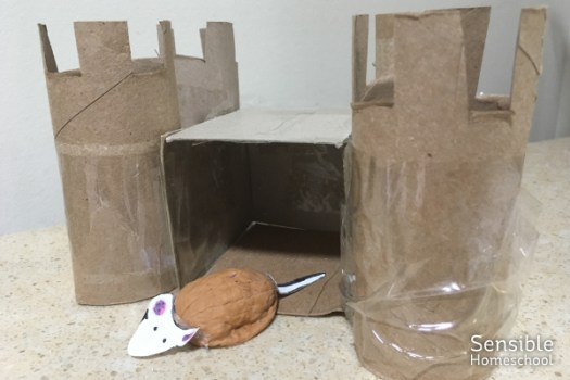 child's craft project - a mouse made from walnut shell in cardboard castle