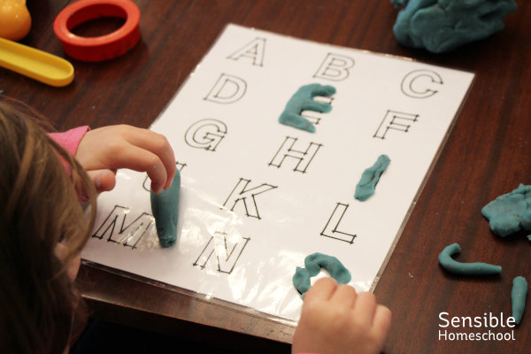 Preschool homeschooler practicing letter formation with blue play-doh on alphabet mat