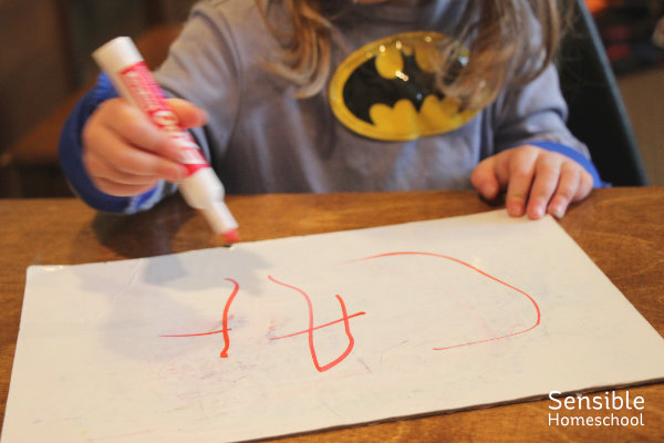 "Preschooler dressed as batman spelling ""cat"" on whiteboard"