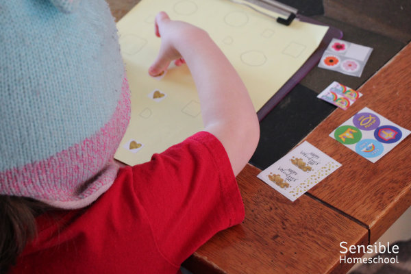 Homeschool preschooler working with stickers at living room coffee table