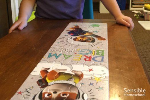 Homeschool preschooler with finished Paw Patrol puzzle on piano bench.