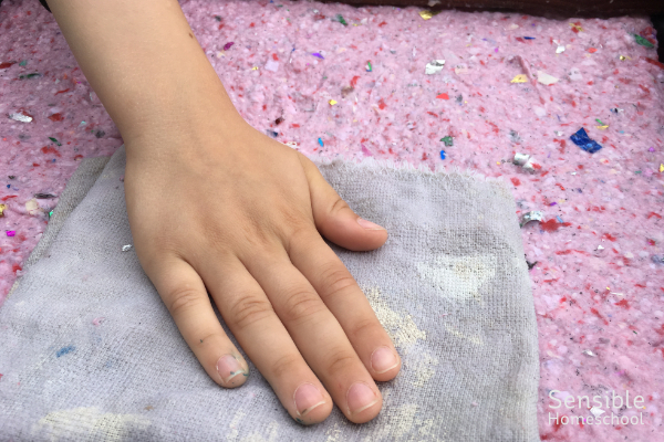 Boy blotting homemade pink paper pulp with rag