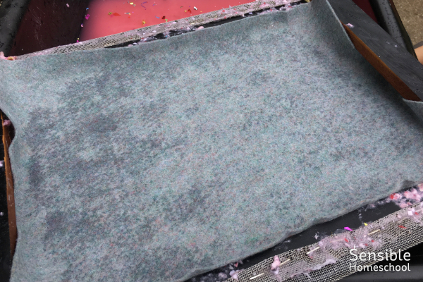 Felt rectangle pressed down on wet paper pulp on paper-making screen