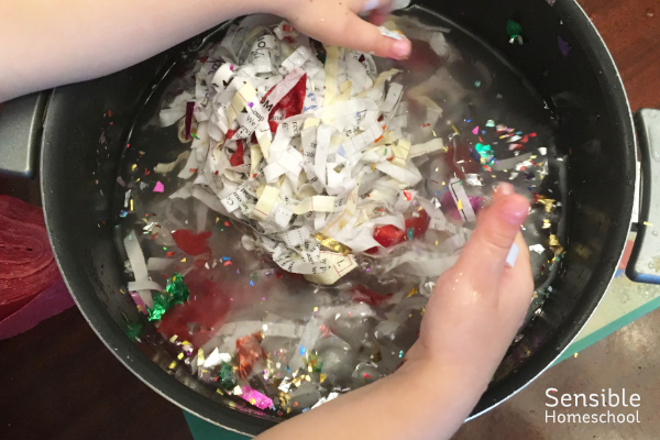 Preschool girl mixing bowl of water, paper scraps and glitter