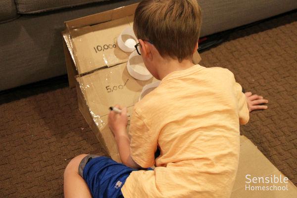 Boy working on making DIY skee-ball game