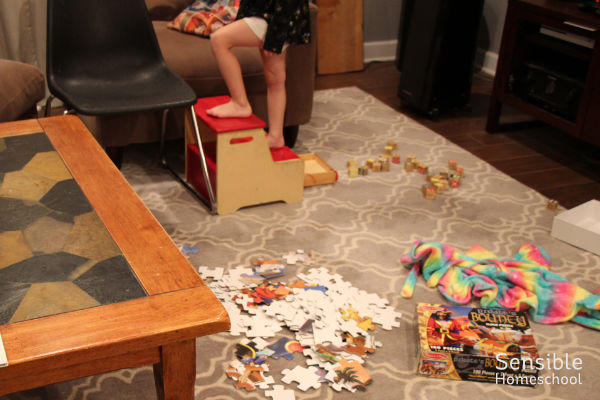 living room with mess of toys, puzzle and preschooler stepping up a stool