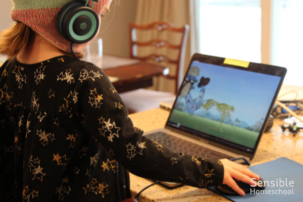 4 year old watching Wild Kratts on a laptop with headphones