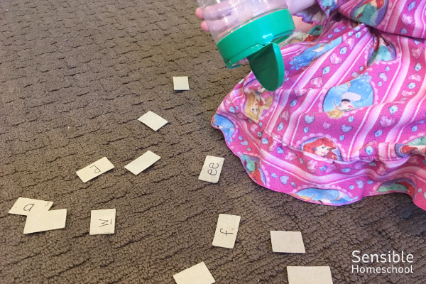 Preschool girl shaking phonogram cards out of container while playing Phonogram Sound Shake