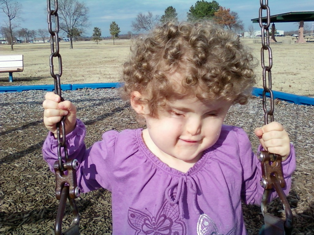 little girl with curly hair on swing