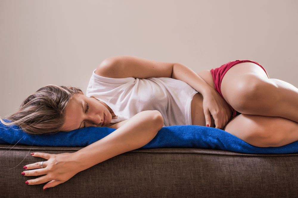 Young woman with sad expression experiencing period pain