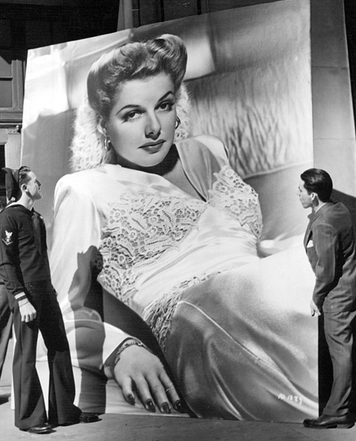 """An eight-feet by ten-feet picture of Ann Sheridan rests outside a Warner Bros. office in New York City before being sent to the soldiers of Little Norway, Canada. Sheridan plays a Norwegian freedom fighter in """"Edge of Darkness."""" April, 1943."""