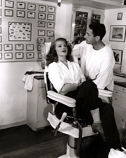 Rita Hayworth gets her make-up done. Notice the lips on the wall. Something for everyone.