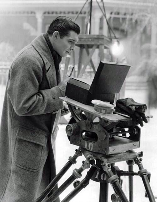 A young Clark Gable checks his hair and makeup on location.