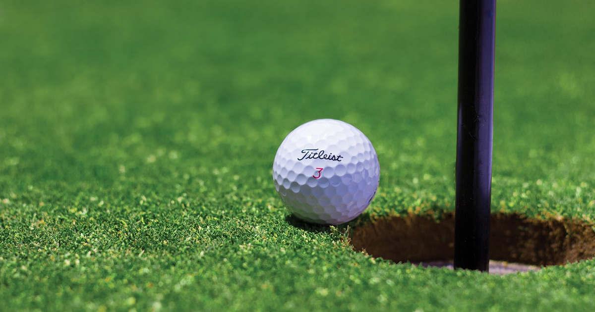 Pallina da golf che sta per entrare in buca