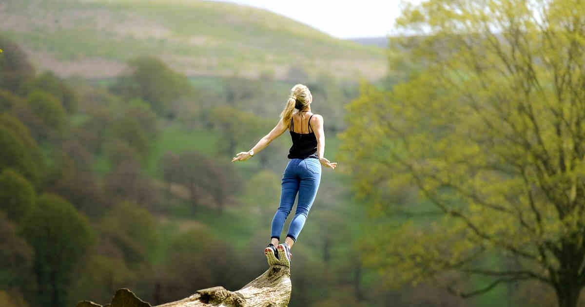 Ragazza in equilibrio su un tronco d'albero