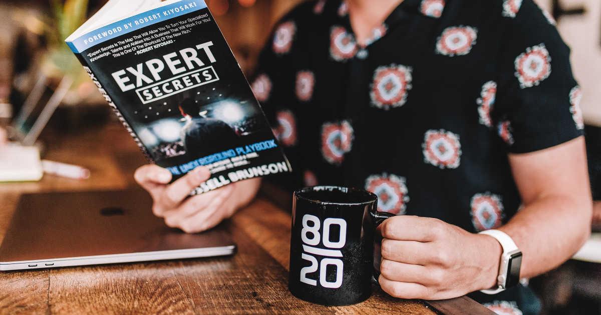Un ragazzo con un libro in una mano (Espert secrets) e una tazza con scritto 20-80 nell'altra.