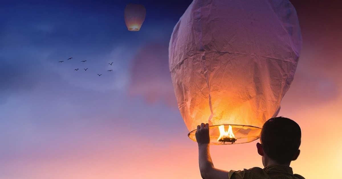 Un bambino che lancia una lanterna luminosa