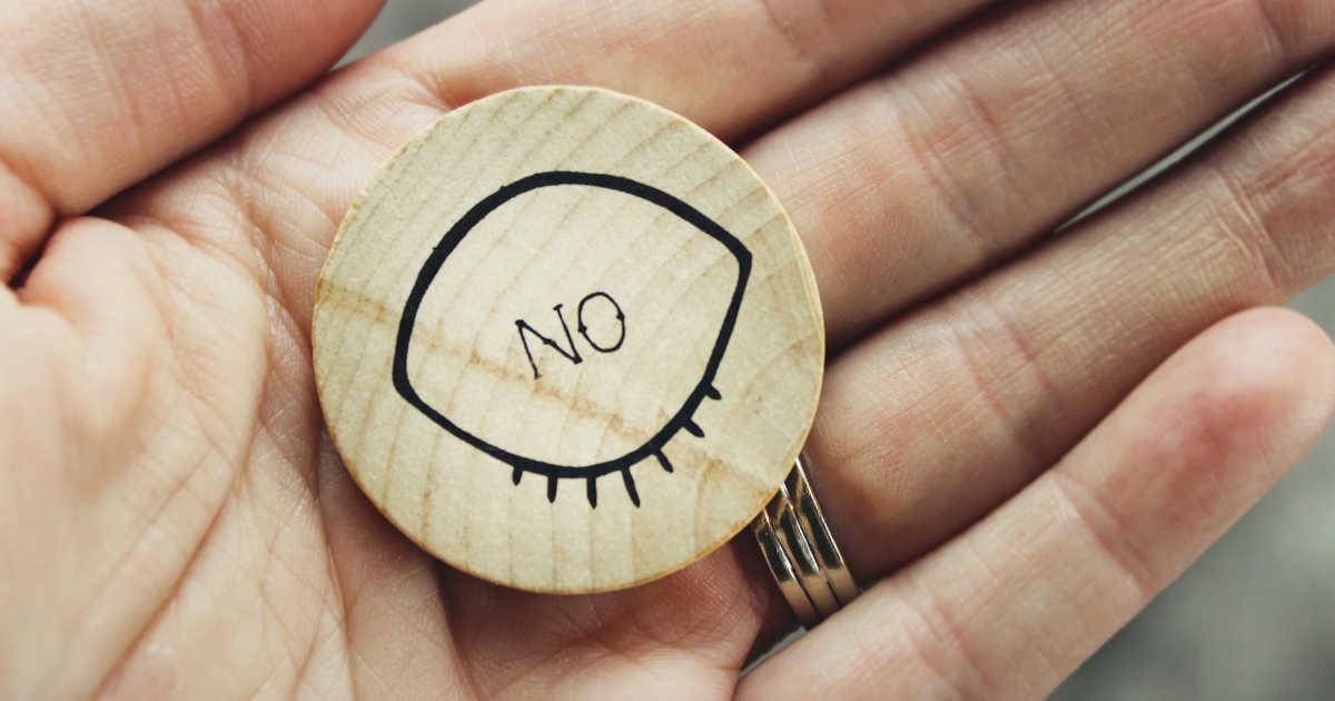 """Mano aperta che tiene un pin di legno con scritto """"no"""""""