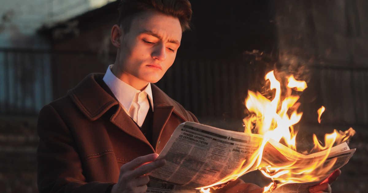 Un uomo che legge un giornale in fiamme