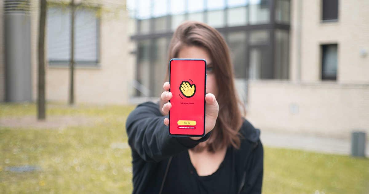 Ragazza con uno smartphone in mano che le copre la faccia