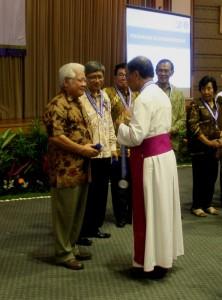 Yusma menerima medali penghargaan dedikasi di yayasan bhumiksara mei 2013