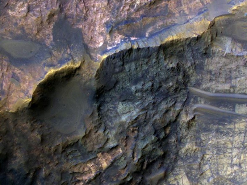 Ancient layered clay-bearing bedrock (top left) and carbonate bedrock (bottom right) are exposed in the central uplift of an unnamed crater approximately 42 kilometers in diameter in eastern Hesperia Planum, Mars. The image was taken by the High Resolution Imaging Science Experiment (HiRISE) instrument aboard the Mars Reconnaissance Orbiter. Credit: NASA/JPL/University of Arizona