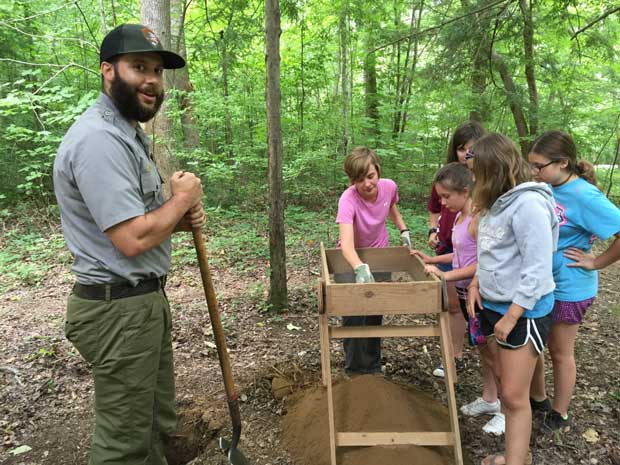 National Park Adventure Campers assist park staff look for artifacts while excavating archaeological test pits with Park Archaeologist Heath Bailey and Student Conservation Association Intern, Josephine Smith. NPS Photo.