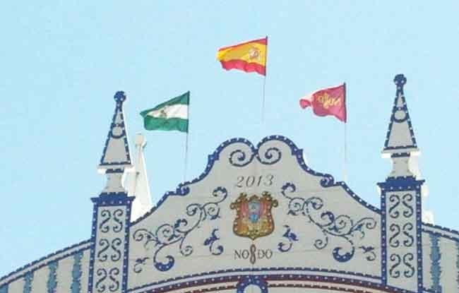 Las tres banderas lucen en el centro de la portada de la Feria de Abril desde esta mañana / Rubén Reina (@al_lawro)