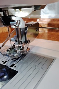 "Using the walking foot, means taking off the shank that supports the regular feet and inserting the walking foot unit and the backwards ""C"" clamp to the screw that holds the needle. Also, the bar inserted behind this walking foot holds down the fabric while the walking foot moves over the fabric as it sews."
