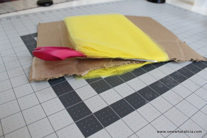 pictured tulle on a cardboard template with scissors