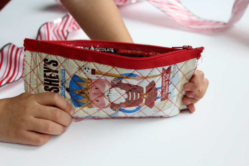 Iron on Vinyl Candy Wrapper Zipper Pouch Tutorial : Use your candy wrappers to create a fun zipper pouch! These will make great stocking stuffers, fill them with candy or toys! Click through for the full tutorial. | www.sewwhatalicia.com