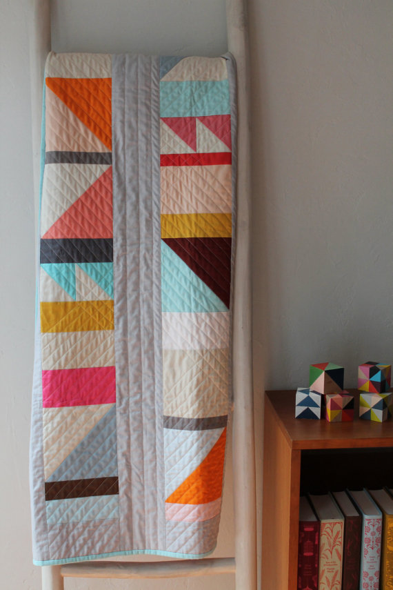 pictured modern quilt hanging on a quilt ladder