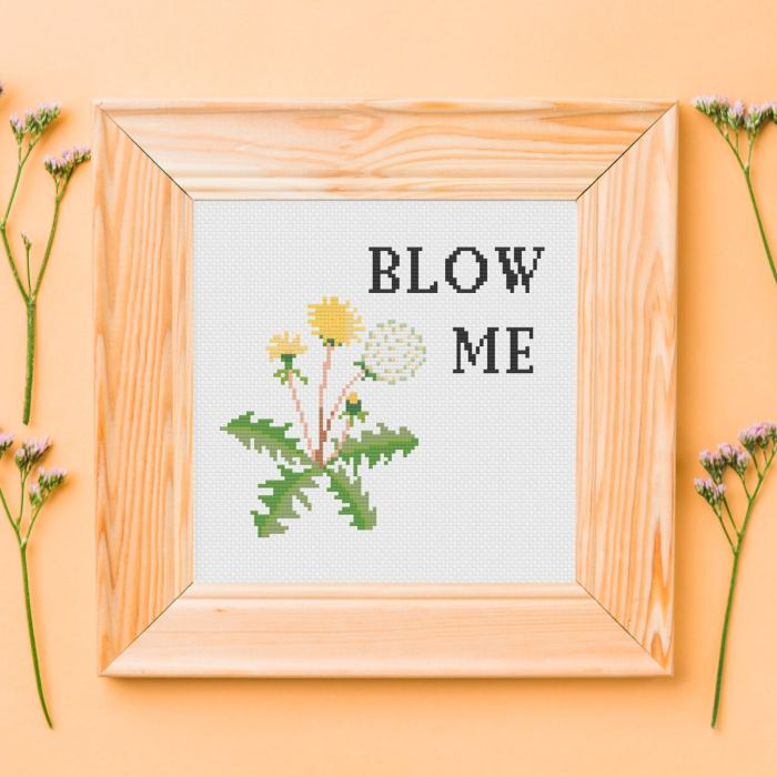 pictured framed cross stitch with a picture of a dandelion and wording blow me