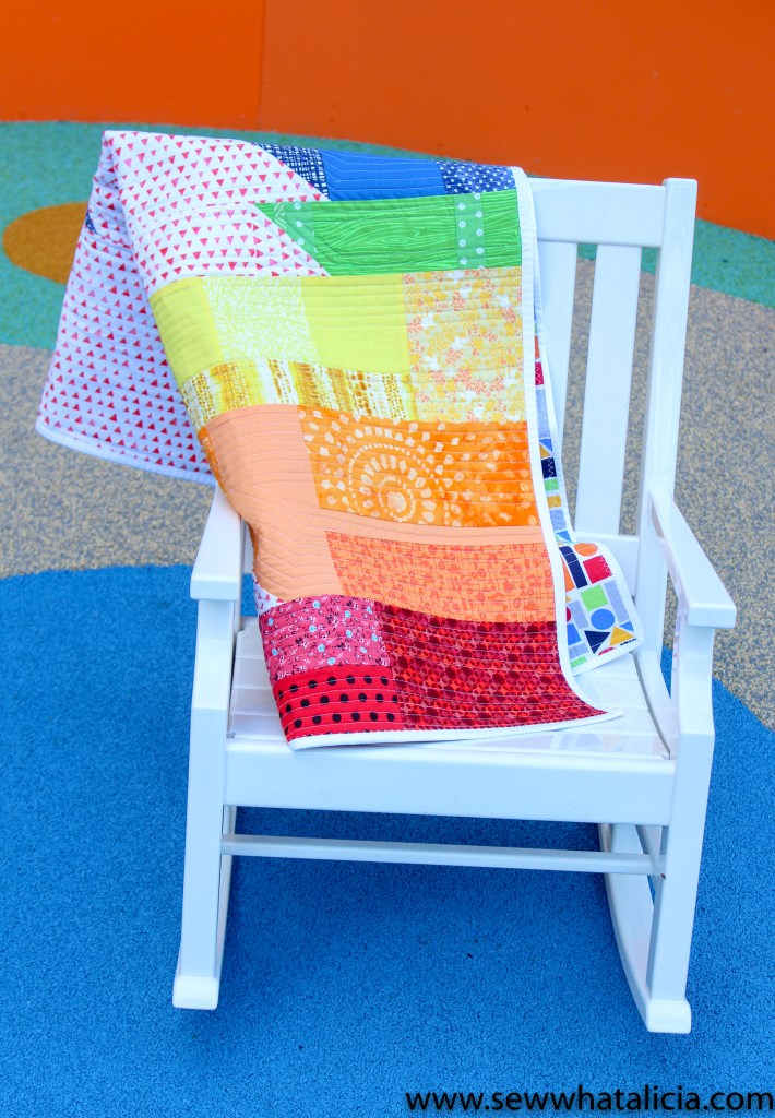 pictured: rainbow quilt on white rocking chair