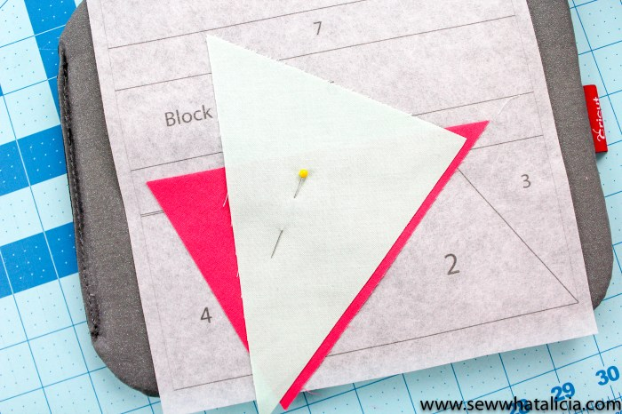 pictured: aqua triangle over pink triangle held together with a pin on top of the quilting template.
