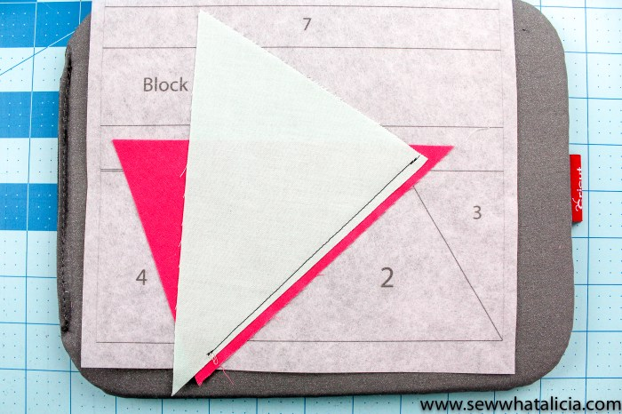 pictured: two triangles and quilt block template with one seam sewn.