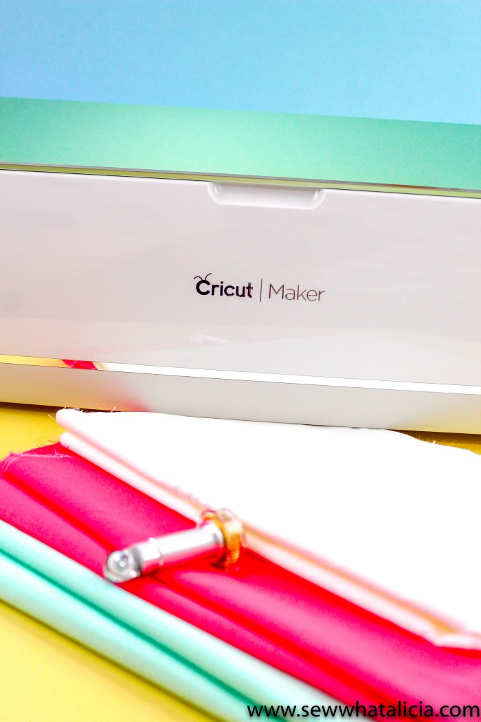 Pictured Mint Colored Cricut Maker, bright fabrics, and Maker rotary cutter.