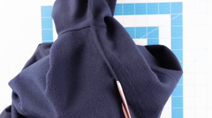 pictured cutting along seam of sweatshirt